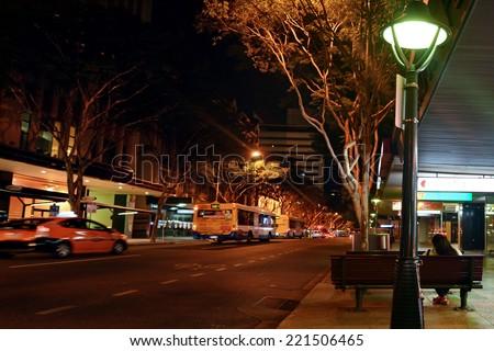 BRISBANE - SEP 25 2014:Woman waits for Brisbane Transport Bus at night.Brisbane Transport operating bus services under the TransLink integrated public transport scheme in Brisbane.