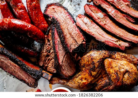 Brisket, pork ribs, beef ribs, chicken, pork sausage. Barbecue meat platter served with classic bbq sides Mac n cheese, cornbread, coleslaw & beer. Classic traditional Texas meats & side dishes. Foto stock ©