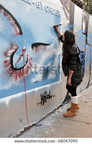 BRISTOL - SEPTEMBER 26: A street artist writes poetry on a graffiti piece in the Stokes Croft area of the city on September 26, 2010 in Bristol, UK. Bristol is famed for its graffiti art.