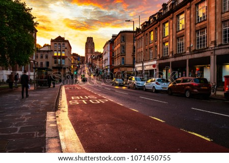 Bristol, UK. Famous street in the center of Bristol, UK in the evening during the colorful sunset. Bright cloudless sky at night. Various shops, cafes and restaurants.