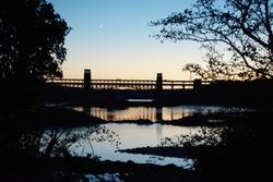 Britannia bridge and Menai Strait with crescent moon as sun sets