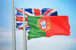 British and Portuguese flags amid blue skies
