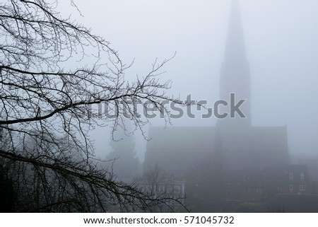 British cathedral silhouette through the dense fog. Concept mystery, thriller, horror, halloween.