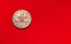 British coin 2 pence (2001) isolated on red background with blurry and space for copy text. Front side of two pence coin. coins collectors wolrdwide.