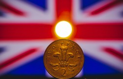British coin 2 pence (2001) isolated on (UK) United kingdom flag background and lighting with space for copy text. Front side of two pence coin. England coins collectors world wide.