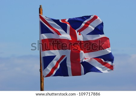 British Flag / Union Jack blowing in the wind against a blue sky