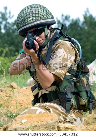 stock photo : British girl soldier in desert uniform aiming her rifle