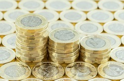 British money, new pound coins in three stacks on a background of more money. New one pound coins introduced in 2017
