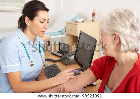 British nurse giving injection to senior woman