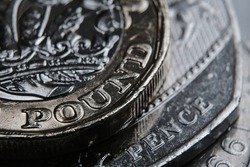 British one pound coin placed on top of fifty pence. The main focus on words Pound and Pence. Selective focus. Macro.