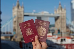British passport held along with other EU passport against London landmark. Travel after Brexit.
