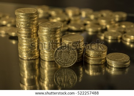 British pound coins neat stacks up close macro studio shot against a shiny reflective black background #522257488