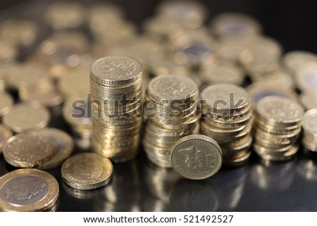 British pound coins up close macro studio shot against a shiny reflective black background #521492527