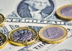 British Pound, Euro coins and US Dollar banknotes in a horizontal color macro picture