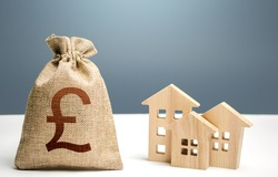 British pound sterling money bag and residential buildings. Mortgage loan. Property tax. Investment in real estate. Purchase of housing. City municipal budget. Costs of service and maintaining.