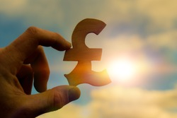 British pound sterling symbol in businessman hand on sunset background, business idea concept, currency, money