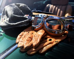 British racing cap, gloves and goggles on a green classic car