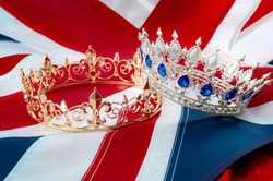 British royals, royal coronation and monarchy concept theme with a gold king crown and a silver queen tiara with the UK flag called the union jack in the background