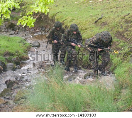 British soldiers move along river bed on training exercise