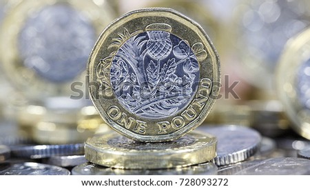 British Sterling. One pound coin standing on other coins with selective focus in a panoramic format #728093272