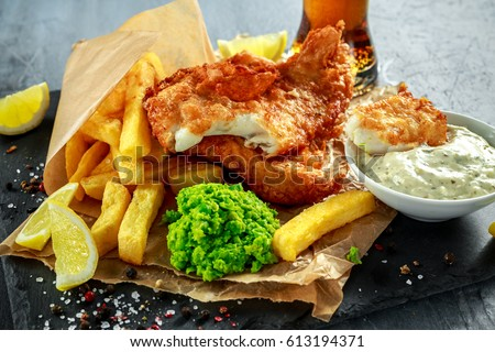 British Traditional Fish and chips with mashed peas, tartar sauce on crumpled paper with cold beer. Stock photo ©