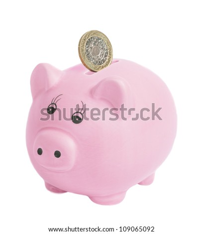 British two pound coin being inserted into piggy bank - isolated on a white bank background
