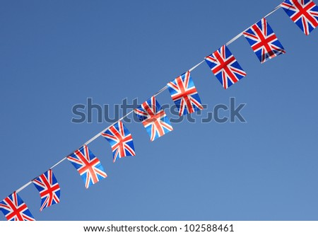 British Union Jack bunting flags against blue sky.