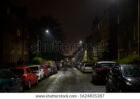 British urban empty streets at night. Dark alley of Edinburgh city with cars parking on the side of the road, damp from the rain. Downtown apartment buildings and homes neighborhood, street lights on.