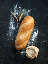 British White Bloomer or European Baton loaf bread on black background. Top view or flat lay. Copy space for text or design. Vertical.
