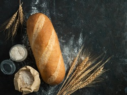 British White Bloomer or European sourdough Baton loaf bread on black background. Fresh loaf bread and glass jar with sourdough starter, floer in paper bag and ears. Top view. Copy space