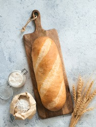 British White Bloomer or European sourdough Baton loaf bread on gray cement background. Fresh loaf bread, glass jar with sourdough starter, flour in paper bag and ears. Top view. Copy space. Vertical