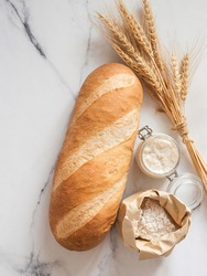 British White Bloomer or European sourdough Baton loaf bread on white marble background. Fresh loaf bread and glass jar with sourdough starter, flour in paper bag, ears. Top view. Copy space. Vertical