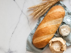 British White Bloomer or European sourdough Baton loaf bread on white marble background. Fresh loaf bread and glass jar with sourdough starter, flour in paper bag and ears. Top view. Copy space