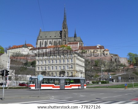 Brno cathedral with red tram passing by