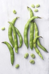 Broad bean or  fava beans (Fave) on the white wooden background, close-up.  From garden to table: springtime vegetables and legumes