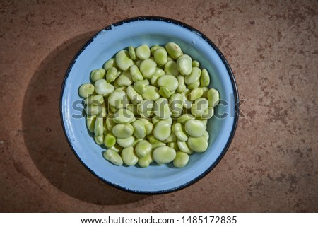 Broad beans are in a blue bowl on the brown table