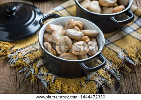 Broad beans served in black bowls. Selective focus.