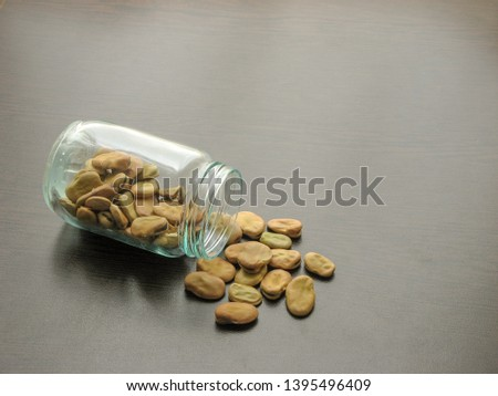 Broad beans (Vicia faba) are poured from a glass jar on brown wooden surface.  Broad beans in a glass jar on the wooden table. Broad beans (Vicia faba) in a glass dish. Wooden background