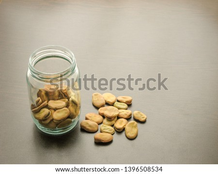 Broad beans (Vicia faba) in a glass jar on the wooden table. Broad beans  in a glass dish. Wooden background. Broad beans are poured on wooden surface next to broad beans in a glass jar.