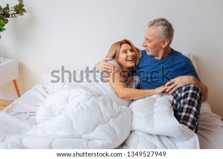 Broad smile. Beautiful dark-eyed wife smiling broadly looking at her man chilling in bed in the morning