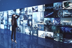 Broadcasting concept with pensive businesswoman looking at media wall with variation of video