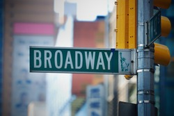 Broadway road sign in Manhattan New York City with skyscrapers.