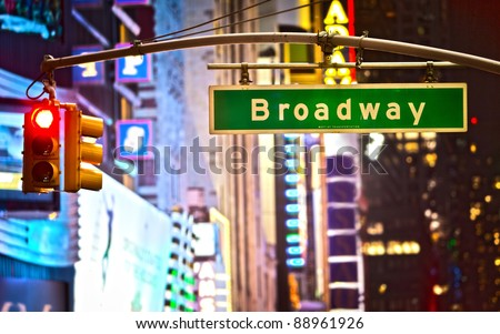 Broadway sign and red stop light in New York City at night - stock photo