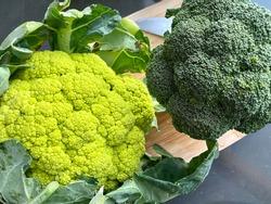 Broccoflower and broccoli on a cutting board