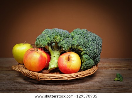 Broccoli and apples in wicker basket