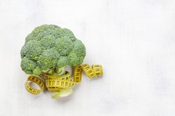 Broccoli and tape measure. Healthy food and weigh loss concept. Diet and fitness. Top view flat lay with copy space