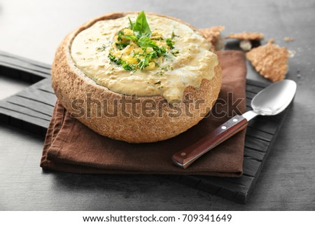 Broccoli cheddar soup in bread bowl on wooden board