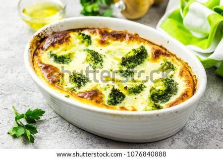 Photo of  Broccoli egg cheese casserole in baking dish on concrete background. Selective focus, space for text.