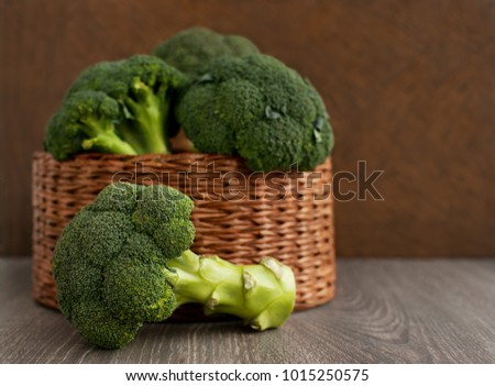 Broccoli in a wicker dish. Broccoli cabbage in a wicker basket and next to snow. Broccoli on a brown background. A lot of broccoli for diet and healthy eating. Vegetables in the basket.