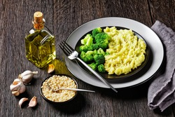 broccoli potato mash sprinkled with chopped almonds served with steamed broccoli florets on a black plate on a dark wooden table